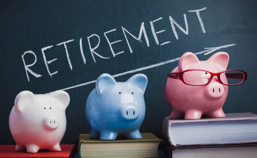 Retirement text on a blackboard with white, blue and pink piggy banks
