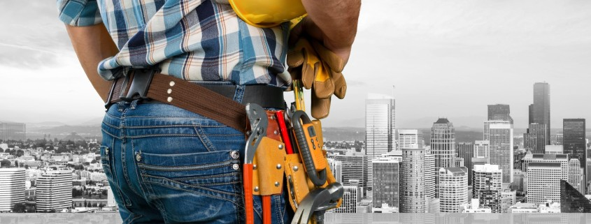 a man dressed in plaid shirt and jeans with a tool belt looking towards a commercial area with plenty of high rise buildings