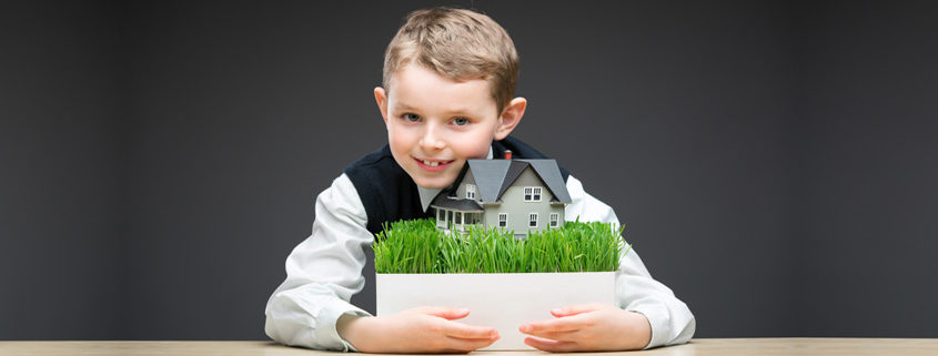 little boy keeping house model on grey background
