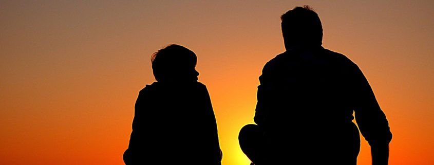 Silhouette of a father and son talking.