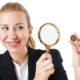 A business woman watching a coin through a magnifying glass