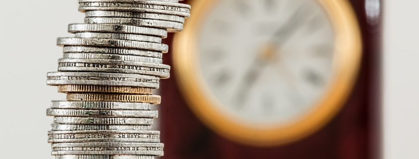 Stacked coins with wall clock in the background